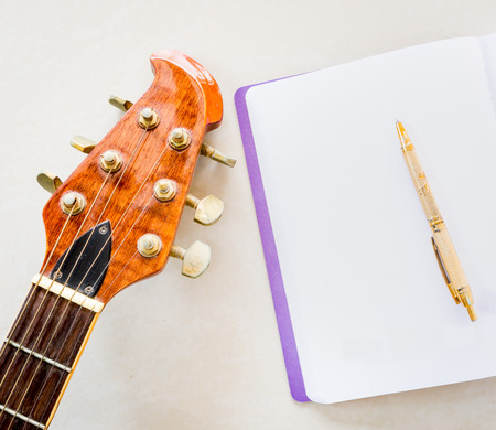 riff: Still life art photography music and memories concept with guitar, notebook, pen and space for write message