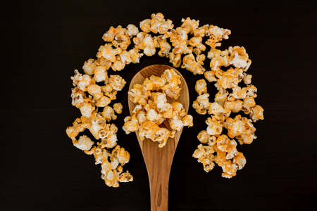 concession: popcorn and wooden ladle scoop on wooden table.