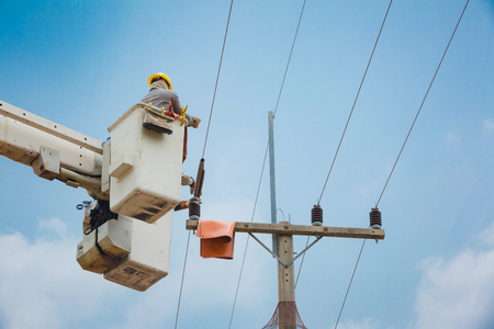 lineman: electricians repairing wire of the power line on electric power pole,22kv.