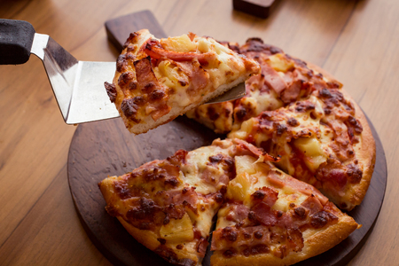 junkfood: Hawaiian Pizza with Pineapple, Ham Slice, Bacon Slice, Mozzarella Cheese, Pizza Sauce on wooden plate.
