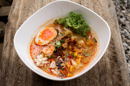 Thai noodle Tom Yum Goong Spicy seafood soup mixed with meat ball noodles, Thai style foods. Stock Photo
