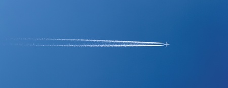 aircraft in a clear blue sky with condensation trail Stock Photo