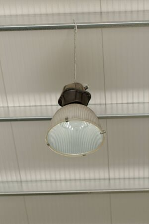 Industrial ceiling reflector with aluminium lamp vessel hanging from the roof Stock Photo - 19745958