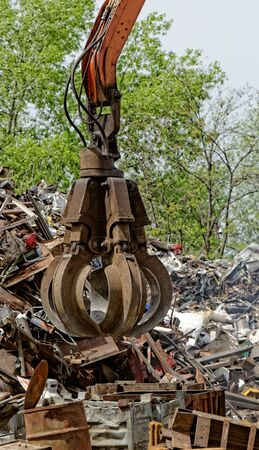 inustrial machine with scrap metal grapple in front of scrap iron photo