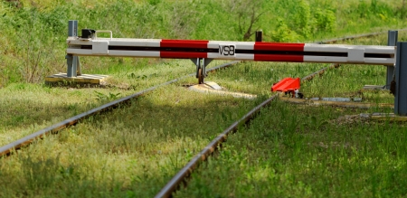 red white barrier to the railroad tracks with grass Stock Photo - 20105661