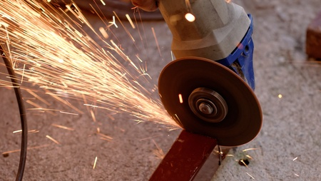 Metal sawing with hand grinder. Sparks while grinding iron. Stock Photo