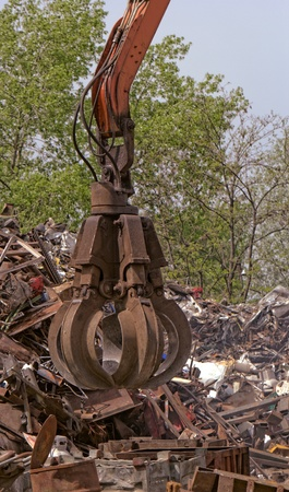 grapple: inustrial machine with scrap metal grapple in front of scrap iron