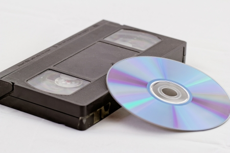 VHS video tape and DVD disk (analog digital) on white background photo