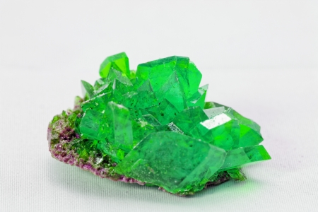 stones: Close up picture about a crystal with emerald color on white background (green crystal) Stock Photo