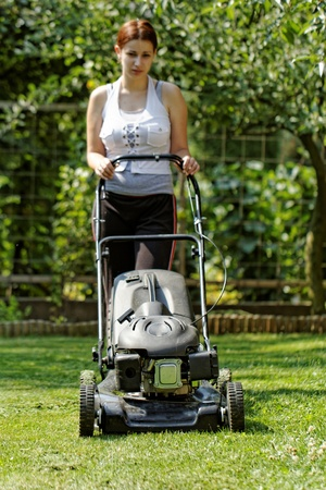 Girl lawn the grass with black lawnmower in the garden (fuel engine) photo