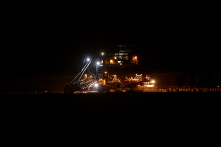 Coal mining in an open pit with huge industrial machine at night shoot photo