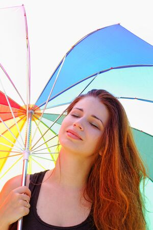 beautiful young girl with rainbow colored umbrella photo
