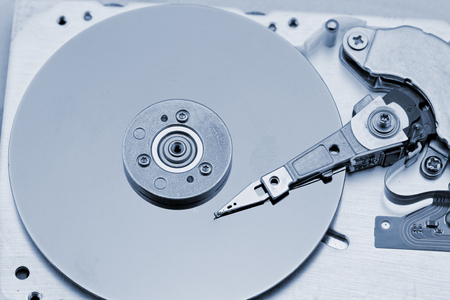 Open computer hard drive on white background with blue (HDD, Winchester) photo