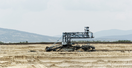 Coal mining in an open pit with huge industrial machine Stock Photo - 22487195