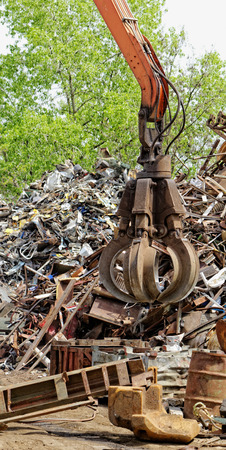 inustrial machine with scrap metal grapple in front of scrap iron