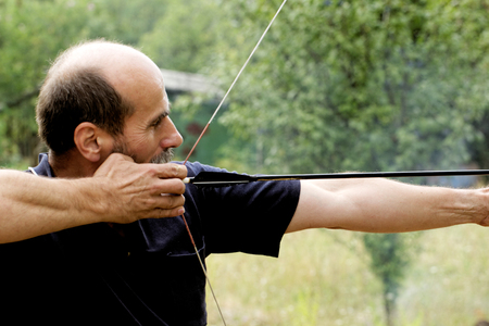 archery man shooting arrow with bow in the nature photo