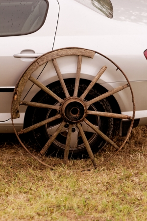 old broken wagon wheel side by new cars back Stock Photo - 22747029