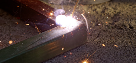 Iron welding with bright light and smoke at manufacturing photo