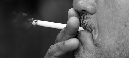 pernicious habit: Man smoking a cigarette against a black background (black and white)