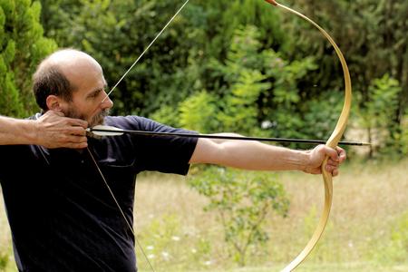 hombre disparando: tiro con arco hombre flecha de tiro con arco en la naturaleza