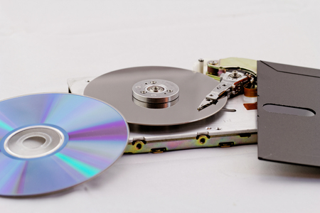 old and modern technics (floppy, cd, dvd, hdd side by side) on white background