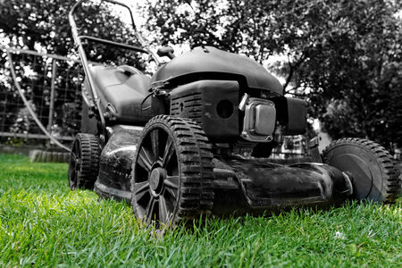 Black lawnmower in the garden lawn the grass with fuel engine bw color photo