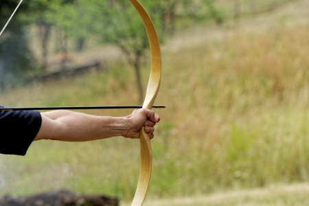 archery target: archery man shooting arrow with bow in the nature
