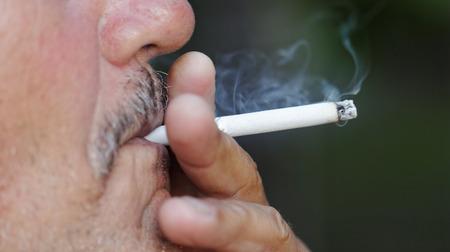 pernicious habit: Smoking a cigarette against a dark background Stock Photo
