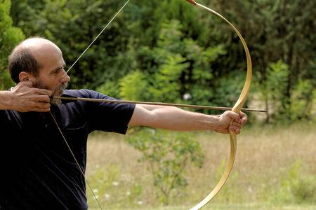 hombre disparando: hombre de tiro con arco tiro con arco flecha en la naturaleza
