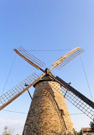 Old wooden windmill against the blue sky photo