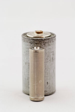 Old grey batteries on white background close up photo
