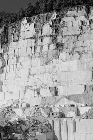 Detail of huge Thassos white marble quarry (mine) with grabber in bw color photo