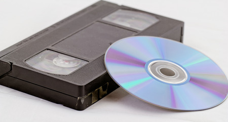 VHS video tape and DVD disk (analog digital) on white background Stock Photo