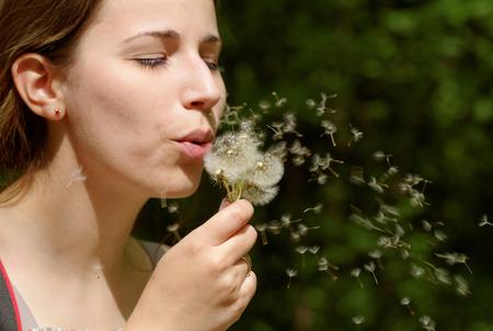 A beautiful woman blow away the blow ball