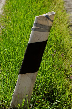 An old damaged column in the green grass Stock Photo