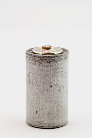 Old grey batteries on white background close up