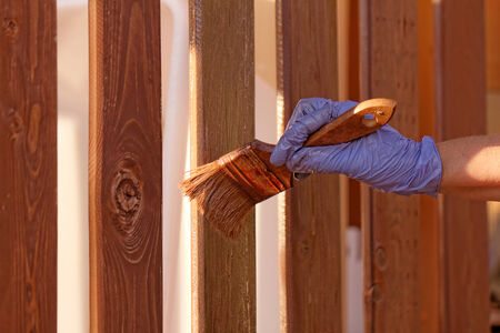 planks fence dyeing with brown paint and brush