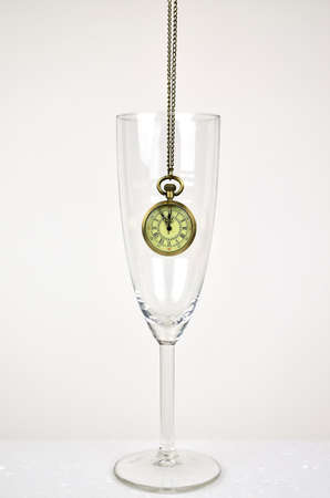 five to twelve: Hanging old watch in a glass of champagne for showing five minutes to twelve. Stock Photo