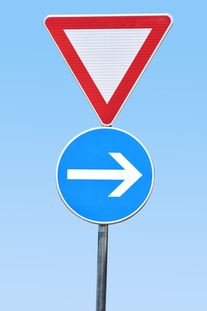 Two traffic signs (Give way/Yield and Turn right) agains blue sky