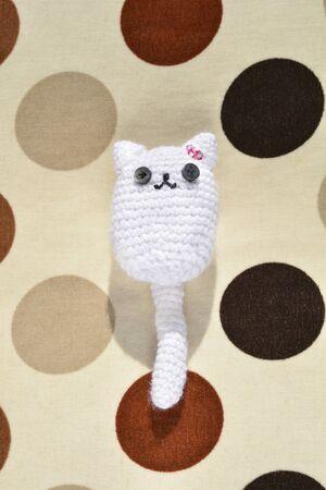 Cute white little crochet cat on polka dot pattern Imagens