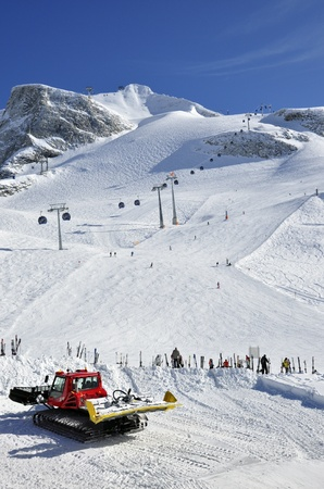 moguls: Hintertux Glacier, gondola cable car, snow groomer, ski runs and skiers in Zillertal Alps in Austria
