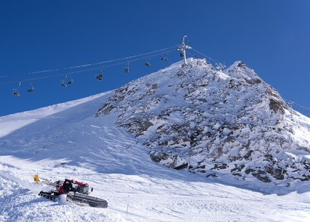snow grooming machine: Chair lift and snow groomer at Hintertux Glacier in Zillertal Alps in Austria