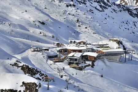 station ski: Ski center at Hintertux Glacier in Zillertal Alps in Austria, with a cable car station, restaurant, bar; gondolas, ski lifts and pistes in sunset light