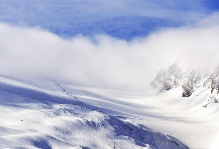 moguls: Hintertux Glacier in Zillertal Alps in Austria in morning fog and sunrise light with ski runs, pistes and ski lifts