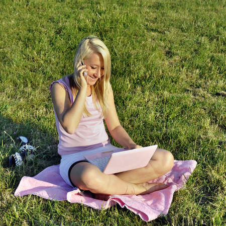 A young smiling relaxed girl sitting cross-legged on the grass on pink towel with pink netbook and talking by the mobile phone Stock Photo