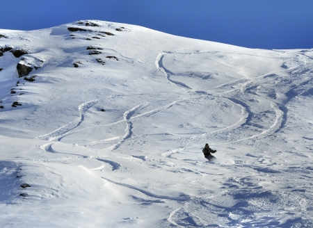 Snowboarder and off-piste tracks on snow in sunset light photo