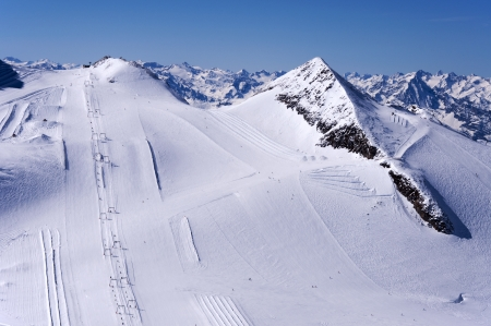 moguls: Skiers, ski lifts, runs and pistes on Hintertux Glacier in Zillertal Alps in Austria