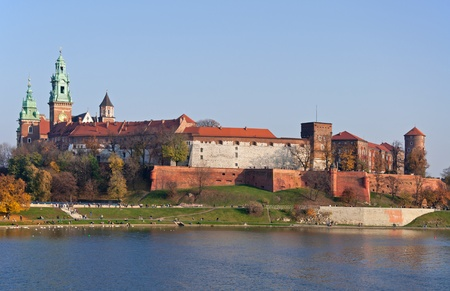 Historic royal Wawel castle in Cracow, Poland with park and Vistula river at sunset