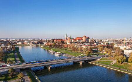 Panorama of Cracow, Poland, in fall, with historic royal Wawel castle, Vistula river and Podwawelski  Bridge. Aerial view from the balloon at sunset,