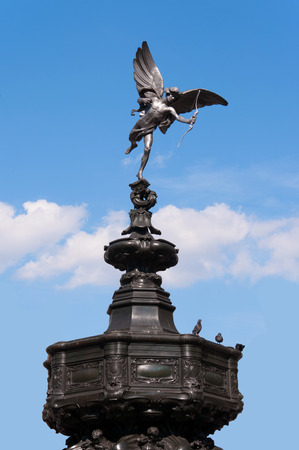 eros: Eros statue on the fountain at Piccadilly Circus in London on blue sky with white clouds